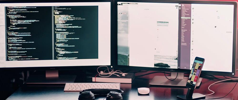 deux écrans d'ordinateur sur une table avec un téléphone et un casque audio