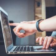 main qui montre pointe l'écran d'ordinateur