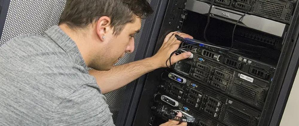 technicien informatique travaillant dans une armoire de brassage de cable réseau