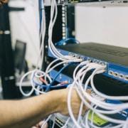 main d'homme plugant des cables réseau