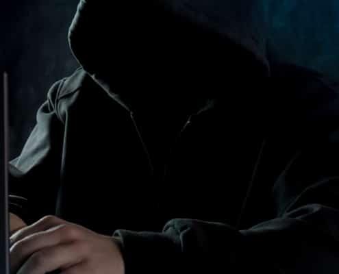 homme avec une capuche qui tape sur un ordinateur