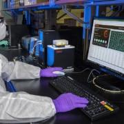 homme avec un masque et des gants qui tape sur un ordinateur