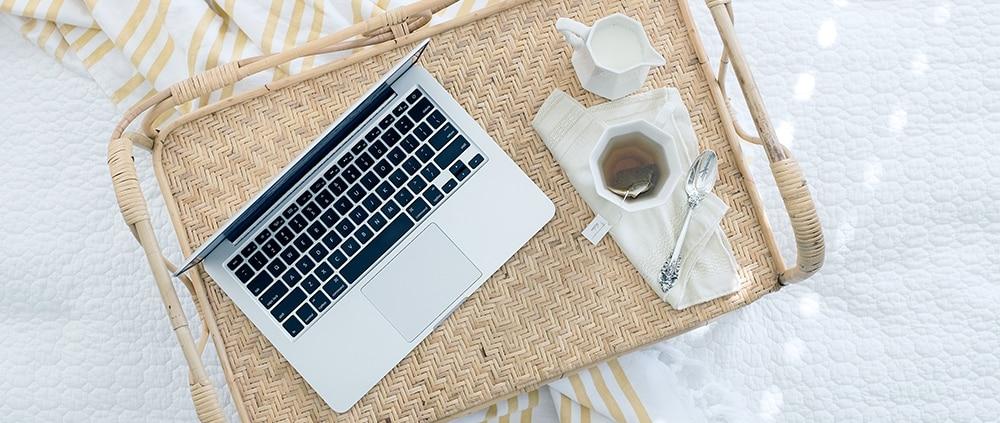 ordinateur portable posé sur un plateau en paille avec une tasse de thé