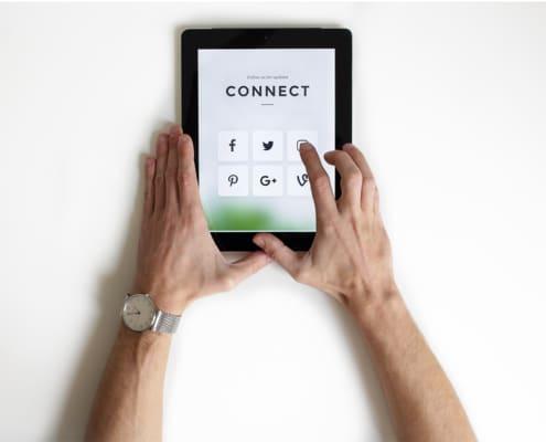 mains d'homme tenant une tablette avec icones réseaux sociaux