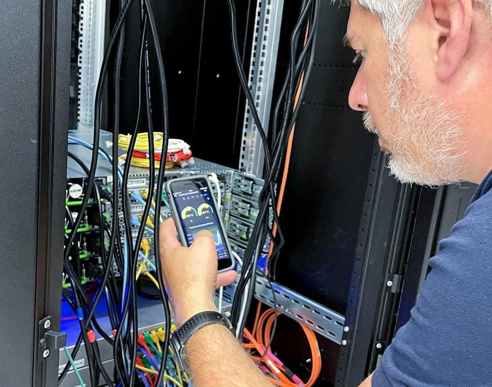 informaticien vérifiant les cables dans une armoire réseau