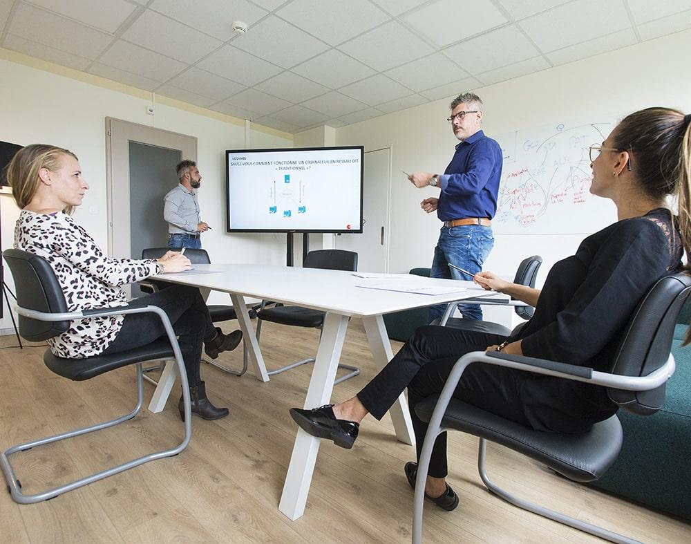 2 femmes assises et 2 hommes debout autour d'une table de réunion entrain de discuter