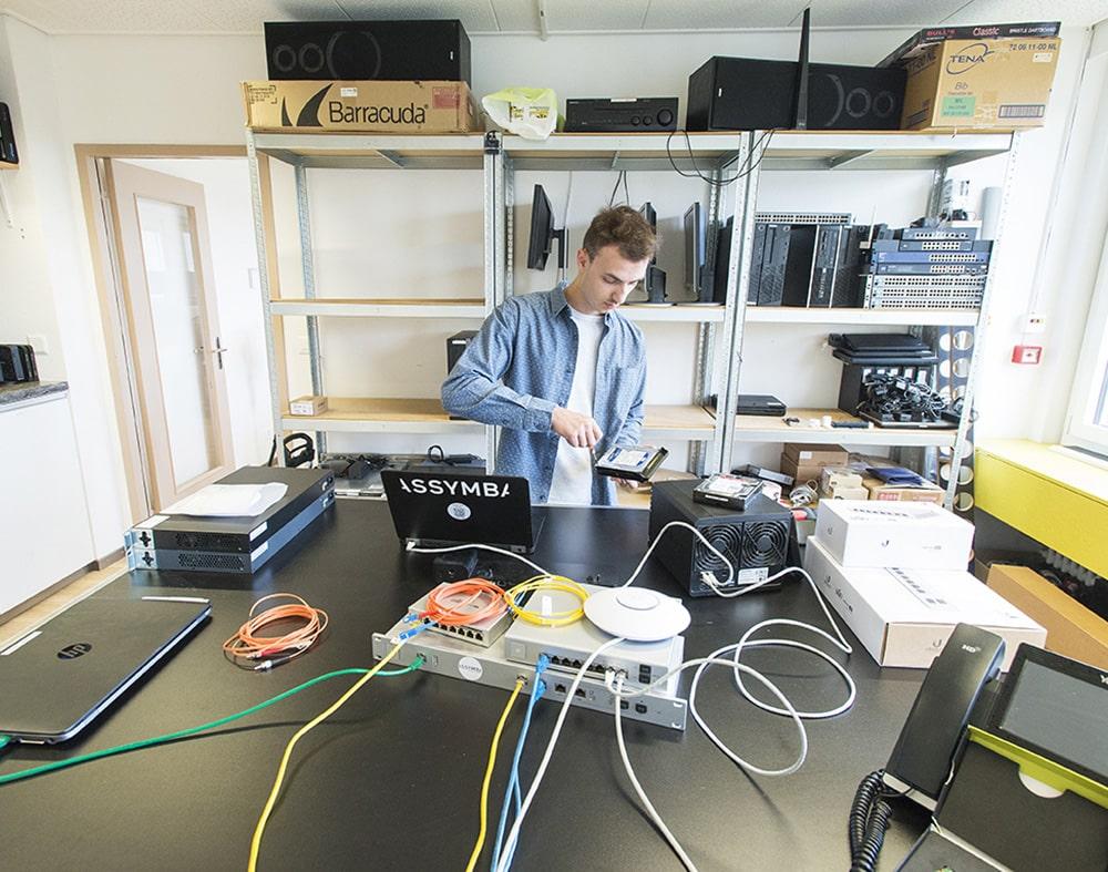 Un technicien entrain d'ouvrir un disque dur à l'aide d'un tournevis