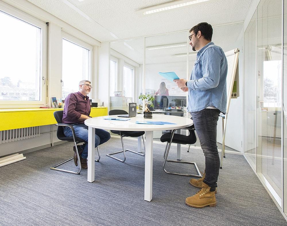 1 homme assis et un homme debout autour d'une table entrain de discuter d'un projet