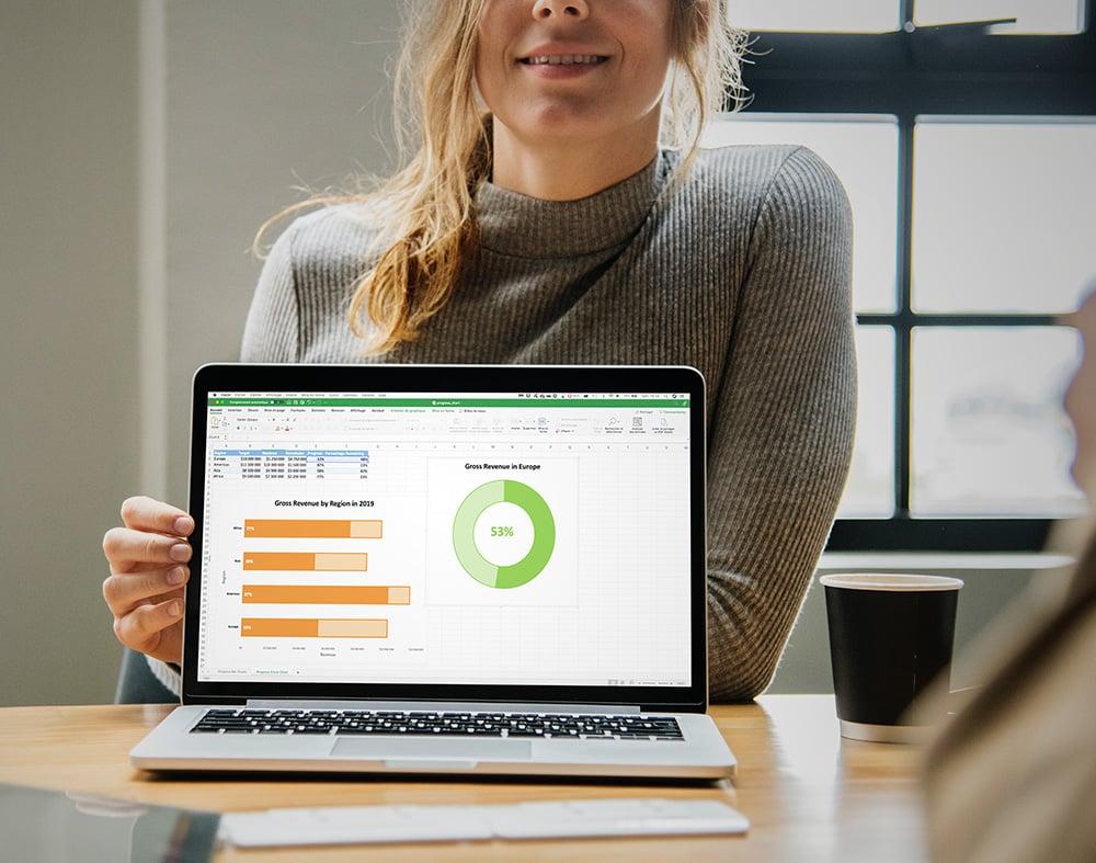 jeune femme présentant son écran d'ordinateur portable avec des graphiques