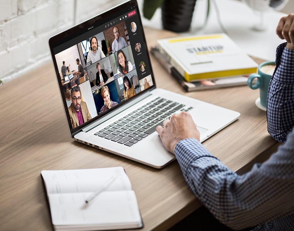 ordinateur portable posé sur une table affichant une réunion virtuelle avec plusieur personnes