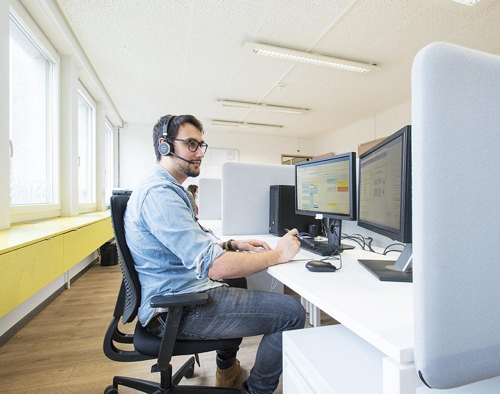 jeune homme portant un casque et micro assis face à deux écrans
