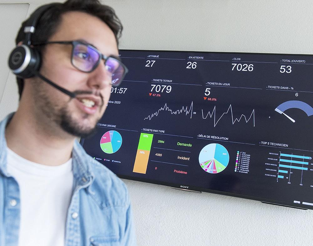 visage flou d'un jeune homme portant un casque et micro et en arrière blanc des données statistiques sur un écran télé