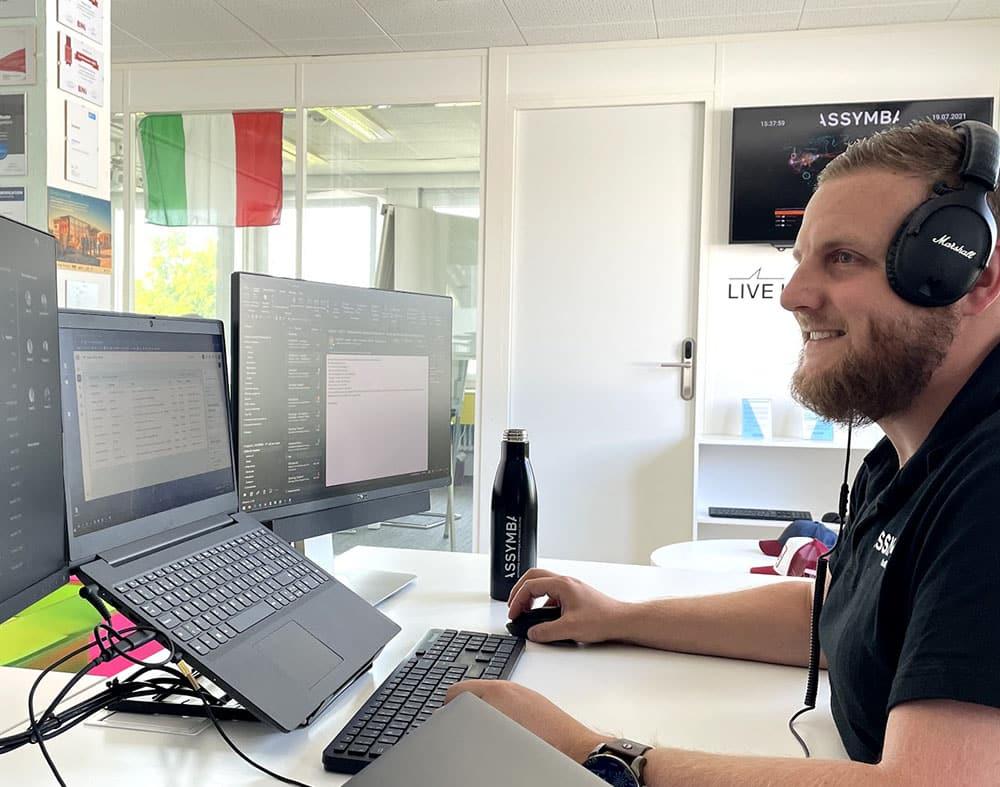 membre de l'équipe assis face à 3 écrans d'ordinateur dans un bureau informatique