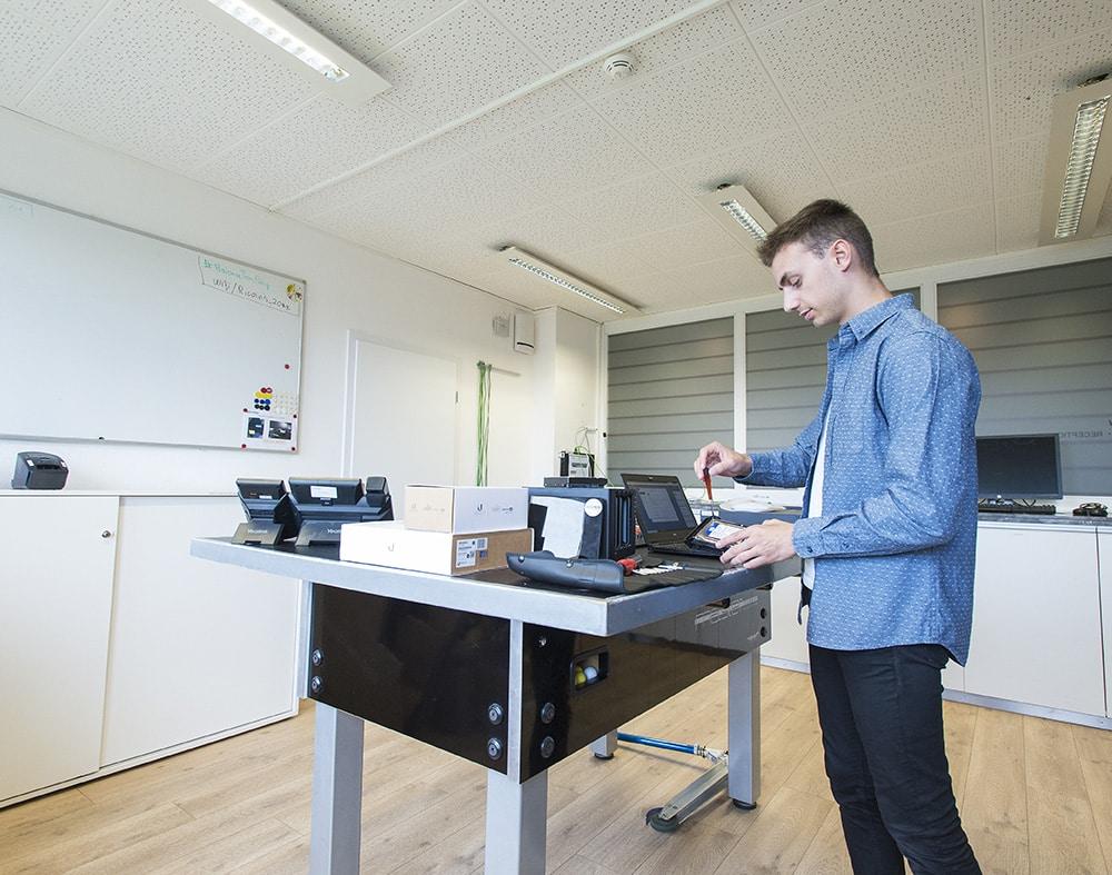 Un technicien entrain de vérifier le fonctionnement du matériel informatique disposé sur la table