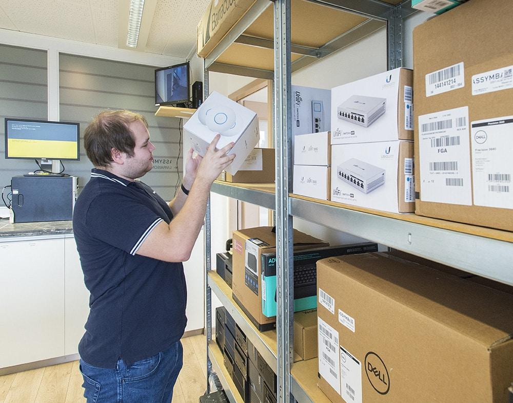 Homme entrain de ranger des routeurs wifi sur des étagères