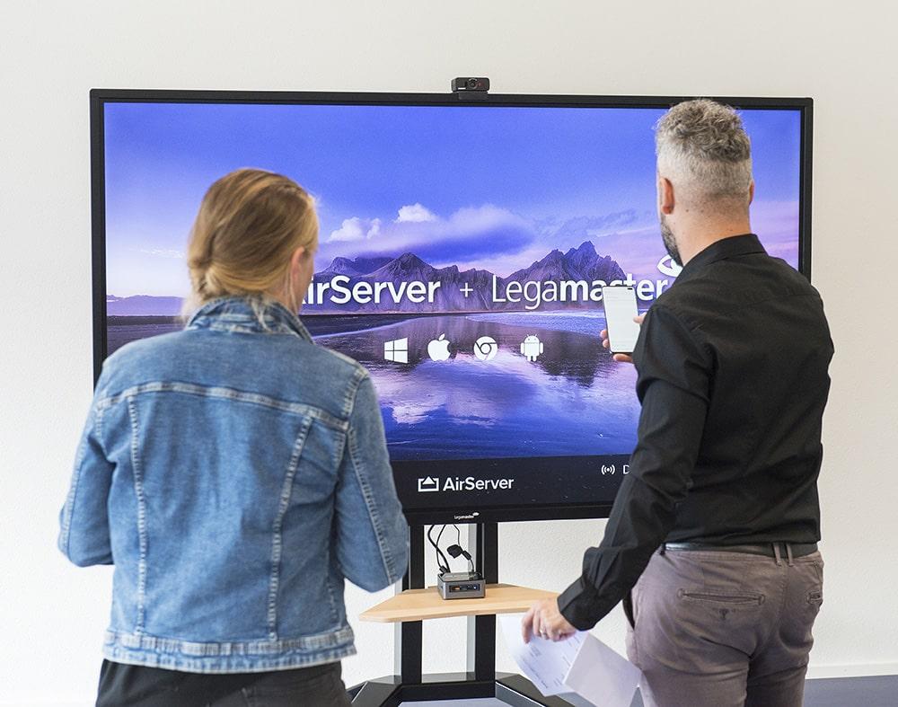 Une femme et un homme devant un grand écran interactifs