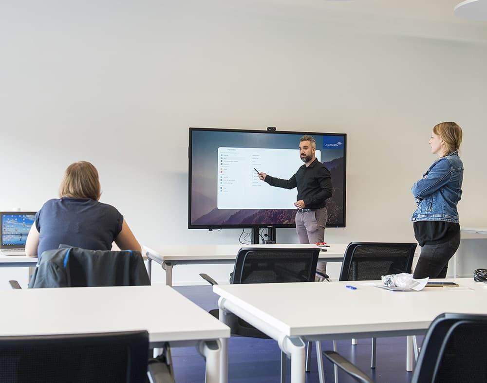 1 femme assise et une femme debout regarde un homme entrain d'interagir avec un écran interactifs face à elles.