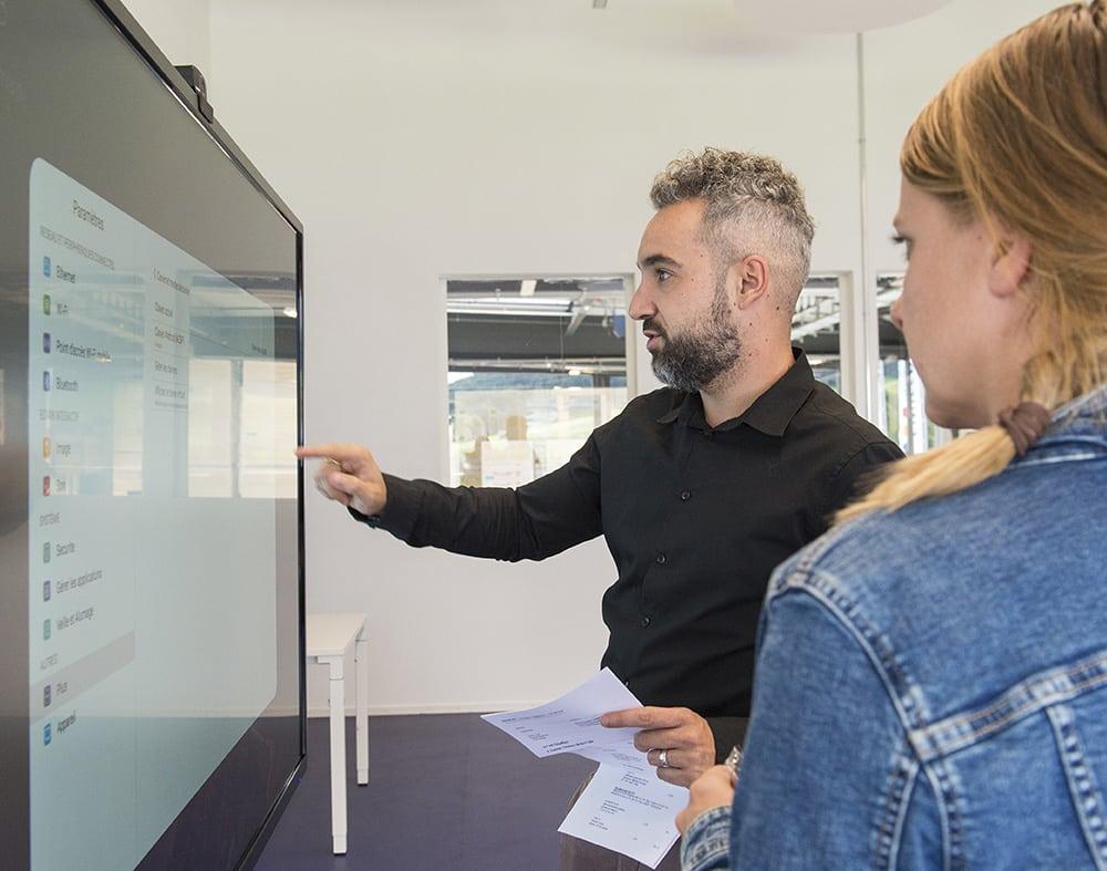photo de profil d'une femme et un homme devant un grand écran interactifs