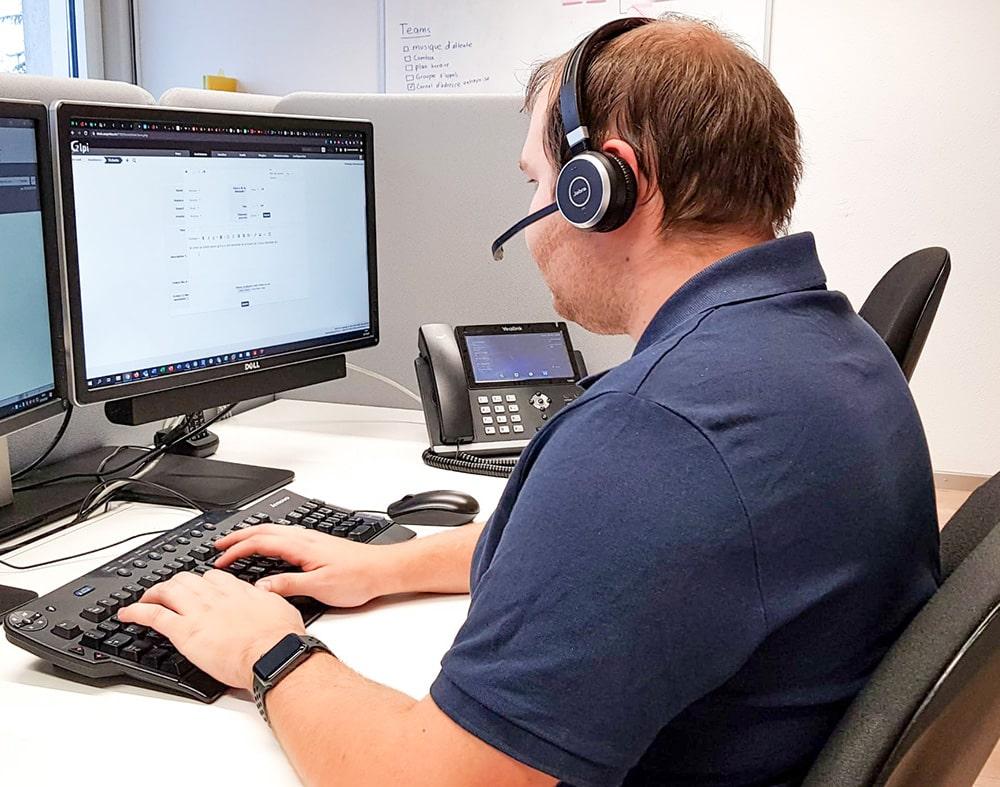 homme tapant sur un clavier assis face à deux écrans ordinateur avec un casque audio sur la tete