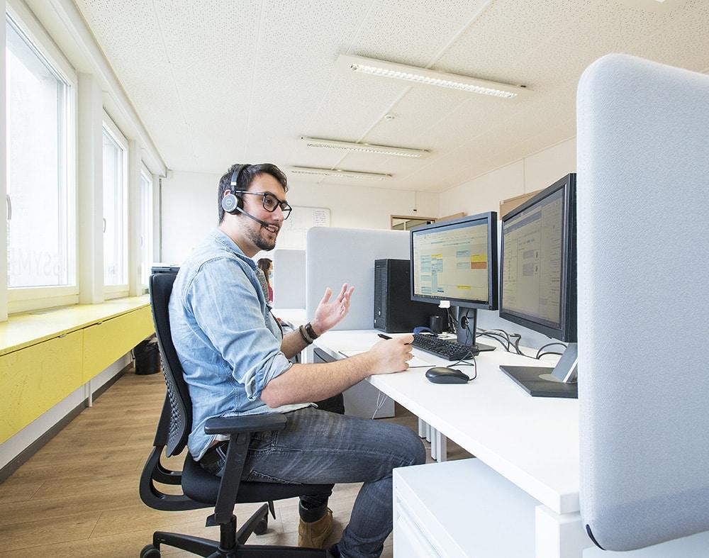 jeune homme assis à un bureau en regardant ses deux écrans ordinateur tout en faisant un appel téléphonique