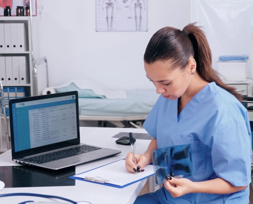 medecin entrain de prendre des notes sur une table dans un cabinet medical avec un ordinateur