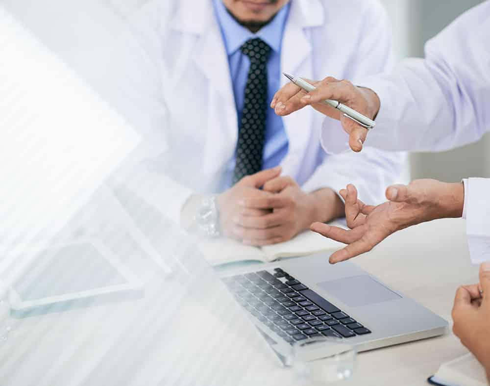 réunion d'affaire entre médecins et un ordinateur sur une table