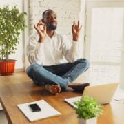 jeune homme assis en position de lotus et avec les yeux fermés sur une table les pieds nus face à un ordinateur portable
