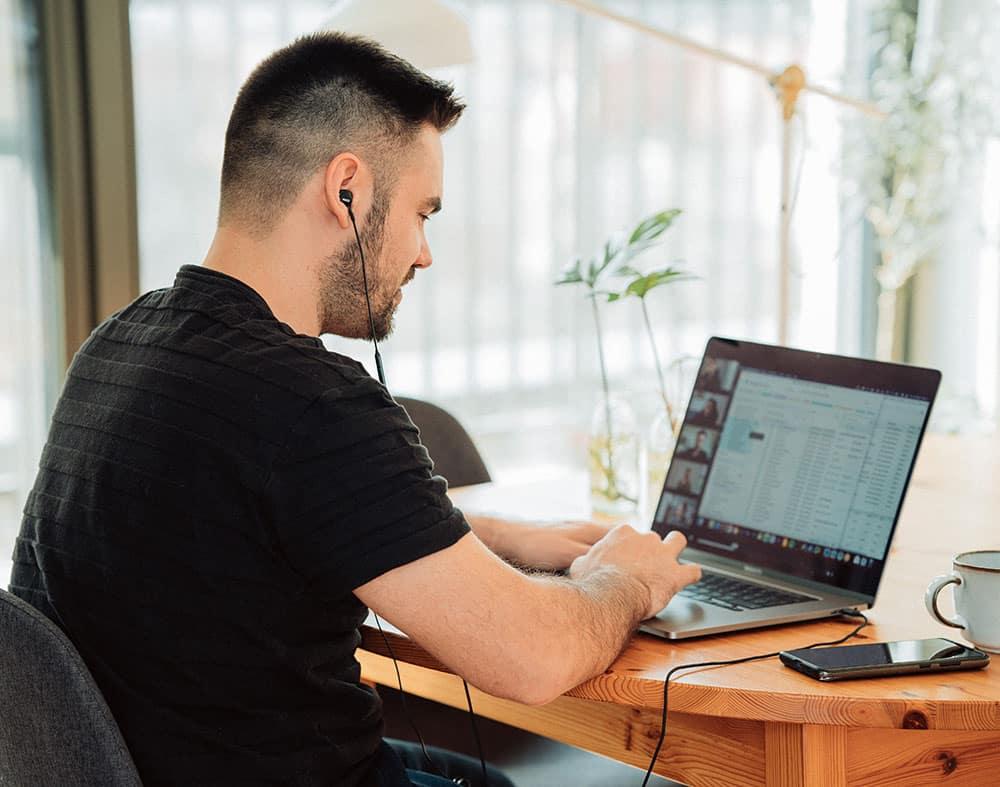 homme assis face à un ordinateur en visio conférence