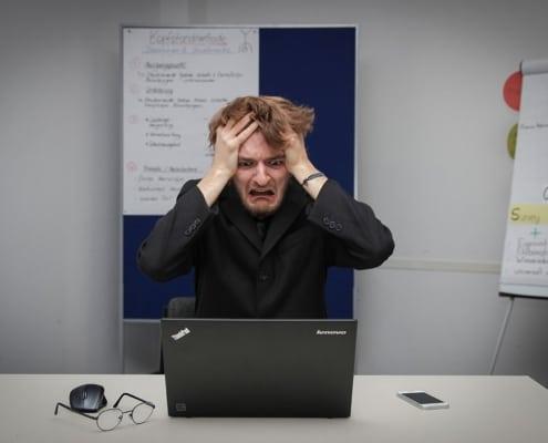 homme se tenant les cheveux avec un tête désespérée assis face à un ordinateur dans une salle de conférence