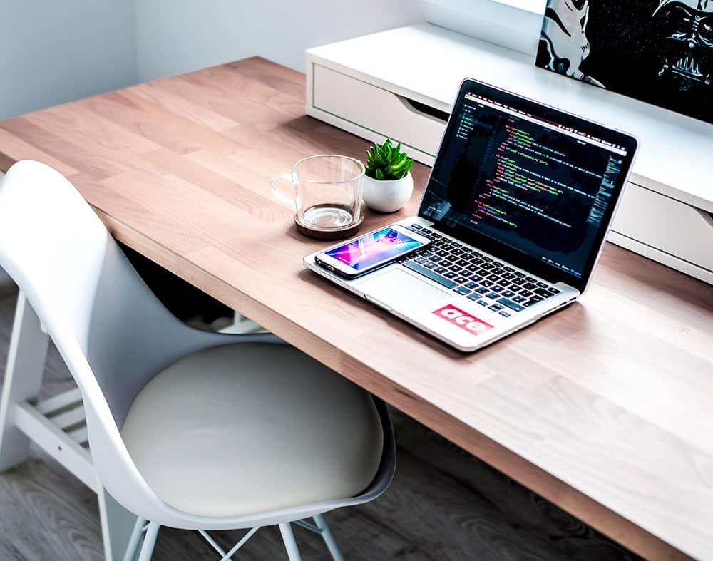 ordinateur et téléphone posé sur une table en bois avec des lignes de code