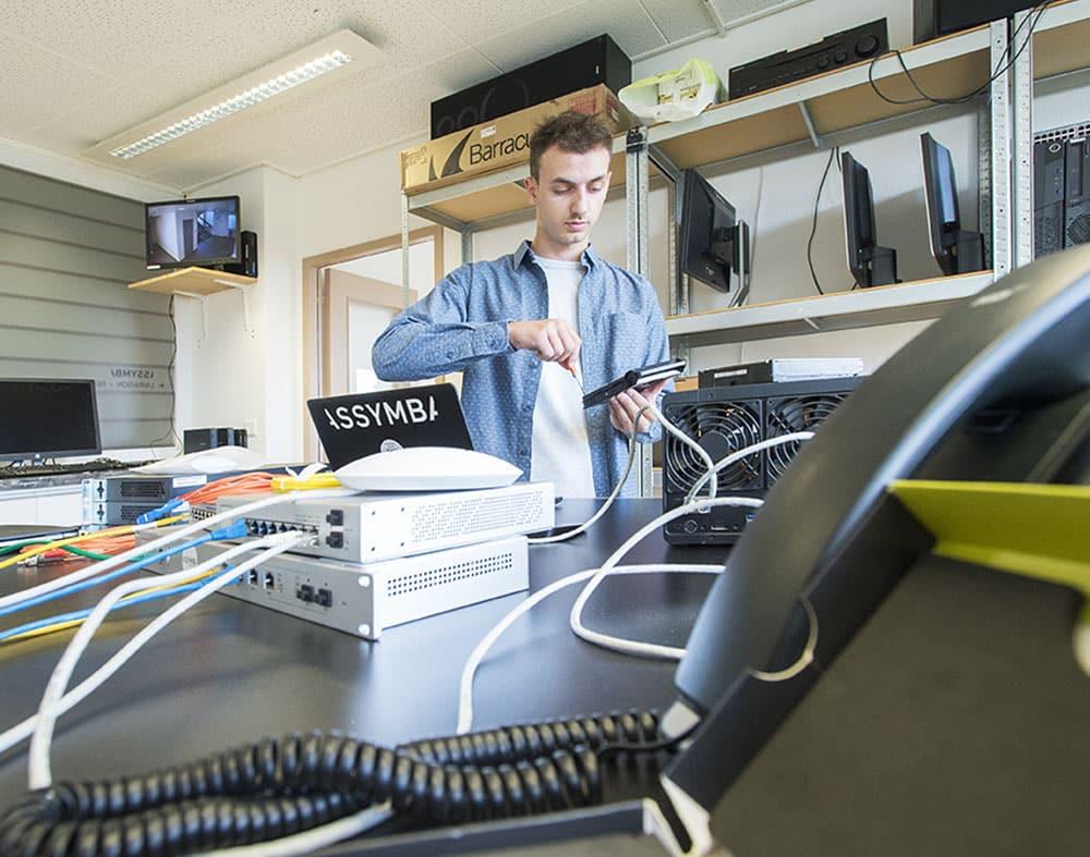 jeune homme informaticien utilisant des outils pour démonter un appareil electronique